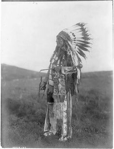 High Hawk, standing, facing left, in ceremonial dress, war bonnet and holding a coup stick - by Edward S. Curtis, Dec 1907