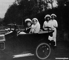 Tsarevich Alexei and his paternal Aunt Grand Duchess Olga Alexandrovna in Alexei's car, Grand Duchess Anastasia and Marie stand behind during WWI