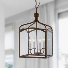 Bring the outdoors inside with this elegant four-light chandelier that is reminiscent of a lantern. It features clear glass sides trimmed by iron with a bronze finish for an old-world atmosphere. Only four 60-watt light bulbs are needed.