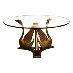 This Mid-Century Hollywood Regency-style brass swan coffee table base is a fabulous statement piece for any living space. The three swan base is in excellent vintage condition with a classic patina and no dents or chips. Please note that the glass is not included. This is a STURDY table that is ready for heavy use.
