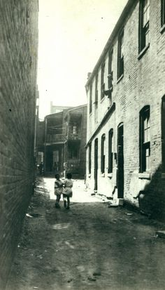 Children playing in an alley of the neighborhood that would become St. Louis' first housing project, Carr Square Village. (1939)