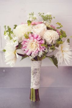 Laura's bouquet featured dahlias, roses, and greenery, all wrapped in lace. |   Photo by Suzanne Rothmeyer Photography,  Bouquets and Boutonnieres by Anna Bee's Floral Design