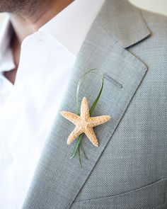 A small starfish and bit of grass decorates this groom's lapel