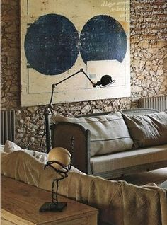 Amazing how the art plays off the texture of the wall ...and the fabric of the furnishings...sculpture's orb..pairs with art-spheres as well...great designing