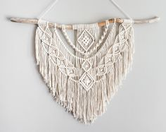 This is a fabulous layered Bohemian large macrame wall hanging and everyone will be astonished by what beauty is on your walls. This is modern macrame at its best. In the center hangs a unique bohemian pendant and sliver beads are used in the fringe at top with beads also throughout this piece. This would look beautiful over your bed, gracing your living room, hallway or anywhere else you want the ordinary transformed into stunning. Original design and crafted by Lucy Lanuza M...