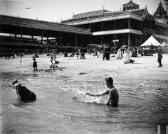 Bathers splashing in the surf as people stroll along the sand w. the enormous Lefferts pier looming in the bkgrd. at Brighton Beach, Brooklyn, New York, July 17, 1886