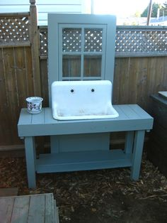 salvaged wood potting bench with re-claimed door & vintage cast iron sink. (I'm hoping the paint will crack a bit during the winter months, then in the spring, it'll be sanded and given an antique glaze)