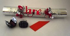 Personalised Christmas Cracker - Made by World of Hampers. This lovely cracker has been filled with a cute little lip gloss purse. Cracker also contains party hat and joke. Men's and children's personalised crackers also available. Need to be pre-ordered for personalisation. Perfect to add to a gift hamper or on it's own. Impress your guests this Christmas with a personalised Christmas cracker. £4.50 plus postage.  Available from www.worldofhampers.co.uk