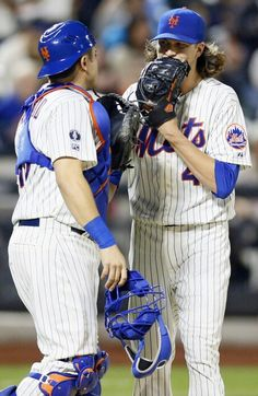 Travis d'arnaud  and Jacob deGrom  have a meeting on the mound.