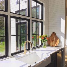 With blue cabinets, white counters and backsplash, and black windows, we felt that using brass fixtures and cabinet hardware was the best way to add some warmth to the kitchen. On cloudy and gloomy days the brass still glows, reminding us of sunny days . 🌞😊🙌 White Farmhouse Kitchens, Farmhouse Windows, Urban Farmhouse, Black Window Trims, Black Windows, Lots Of Windows, Windows And Doors, Bridgewater House, White Counters