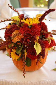 Fall wedding.. Cute idea to put flowers in a pumpkin as a center piece!