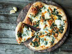 Hvit pizza på grov bunn med spinat og bakt hvitløk