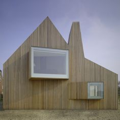 Timber-clad house featuring different shaped windows protruding from its surfaces at various angles on all sides.