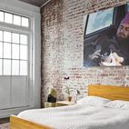 In the guest bedroom, a painting by Monique Crine hangs on the original brick wall above a Miles & May bed and side table. The rug is...