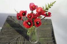 Stems of dollhouse scale corn poppies arranged in a miniature milk bottle made from recycled plastic - Photo © 2014 Lesley Shepherd