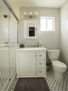 AFTER: Once the wallpaper and carpet were removed, a new vanity, medicine cabinet, and subway tiles in the glass shower were installed to create a bright, modern bathroom.