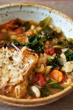 NYT Cooking: Even vegetable stews can have more vegetables. This recipe adds a pound of kale -- that's right, a full pound -- to softened onions, carrots and celery, combined with beans and tomatoes. It's simply a matter of bringing the other vegetables together in a simmer, then adding the kale and topping with the toast. The whole dish bakes in the oven for a few minutes to%2...