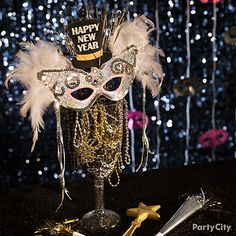 Create this masquerade masterpiece by filling a clear glass with a mix of beads. Perch a feather mask on top and add a Happy New Year cutout to finish it off!