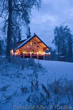 Log Cabin in the woods decorated with Christmas lights at twilight near Fairbanks, Alaska during Winter