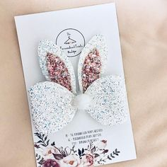 "Our beautiful Lacey hair bow has been blessed with some bunny ears perfect for this Easter. These 3.5 inch bunny ears are placed onto our Lacey 5"" bow, will lots of chunky glitter. Our bunny ear bow comes on a metal crocodile clip. Perfect for this season fashion as well as the"