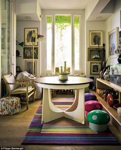 Rosita originally bought this vintage table for her granddaughter but liked it so much she decided to keep it. In the corner is a vintage Arredoluce Monza Triennale brass floor lamp. The pouffes and rug are by Missoni Home, and the toadstool footstools are homemade