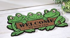 "Welcome to Our Pad Frog Coir Bristles Front Door Mat Outdoor Porch Floor Rug;  Let these silly frogs welcome family and friends to your home! Bright green frogs hold a sign saying ""Welcome to Our Pad"" on this durable coco mat. Coir and plastic. 18"" x 30"""