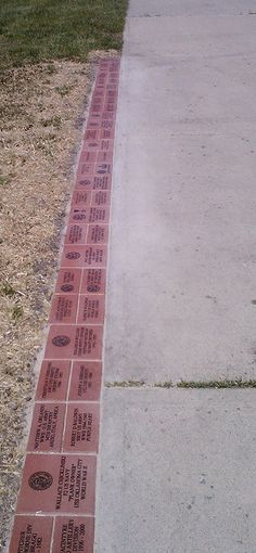 Donor bricks edging existing pathways, installed in dirt/grass. Exterior Signage, Exterior Siding, Wall Exterior, Brick Edging, Brick Walkway, Exterior Gray Paint, Exterior House Colors, Donor Wall, Brick Art