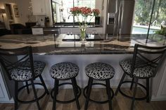 """The homeowners behind this renovation in the Bent Tree Woodlands II neighborhood of Sarasota, Florida call their kitchen island the """"Mystic River"""" because of the dramtatic sweep and color of the veining in the granite."""
