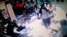 Homem agredindo dona de farmácia em assalto.