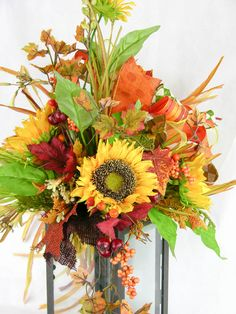 A black metal and glass lantern with a large sunflower swag filled with grasses, honeysuckle vines, and burlap leaves in rust, green and brown. Topped with a six patterned Terri Bow in coordinating ri
