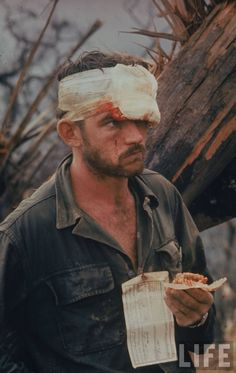 American soldier w. a bandaged head wound looking dazed after participating in Operation Prairie just south of the DMZ .