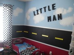 Little Man, This is our sons bedroom.  He loves cars planes and trains.  We wanted to do a room that could grow with him as he is only 2 years old.  The top half of the walls are sky the middle a road using black chalk board paint and the bottom red.  He loves his room!, The is a little boys bedroom with black road around the middle of wall made out of chalk board paint.  , Boys Rooms Design
