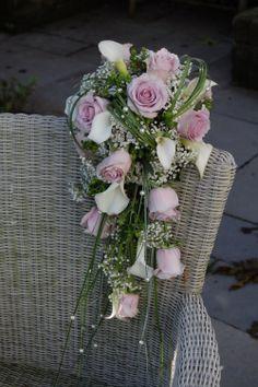 Bruidsboeket in waterval vorm. Lila rozen, wit gipskruid en calla's, berengras. www.meesterlijkgroen.nl