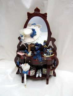 Stylish Ornate Ladies Dresser with Accessories.   The dresser has a rich mahogany coloured finish. It is filled with essential ladies items in shades of blue. Everything is fixed into place. The centre drawer opens to reveal contents inside Also included is also a pretty Umbrella which is loose to display as you wish.