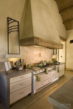 The cooking center in this kitchen anchors one end of a large great room that resembles a converted barn. To enhance the French look, there is a custom provincial-style hood with a heavy wood mantle made from fir milled from a tree on the property.