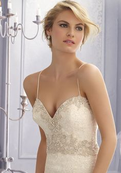 Lace appliques create a beautiful and feminine Bridal Dress. Featuring removable spaghetti straps and a crystal embroidered sweetheart neckline.