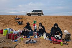 Sisters relax as their children play on the slopes of the desert outside Riyadh in Saudi Arabia. PHOTOGRAPH BY LYNSEY ADDARIO