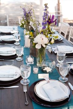 Turquoise, eggplant purple, and cornflower blue with peacock accents on farm table with runner and eclectic wildflowers for Lake Tahoe wedding