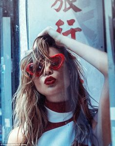 Red hot: In this fun image Behati dons heart-shaped glasses and pouts with bright red lips...