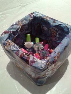 """Smalti colorati in un cestino coperto di carta regalo Frozen per fare l'angolo """"pitturiamo le unghie"""" per la festa di compleanno"""