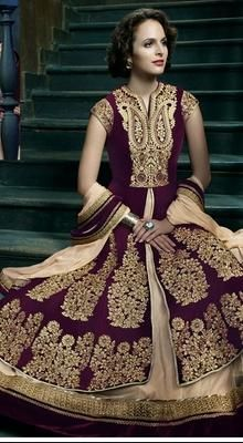 Heavily Embroidered Eggplant Velvet Anarkali Dress with Cap Sleeves Look elite in this eggplant velvet flared Anarkali dress. The neckline and cap sleeves are embroidered with golden thread and stones. The kameez is heavily embroidered in decorative paisley motifs on the upper layer part. Second layer has contrasting hemline which adds elegance to the whole outfit. Comes with matching bottom and dupatta. #LatestNetDesignerAnarkaliSuits #DesignerBridalLadiesSuits