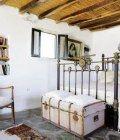 Το ταβάνι με τα καλάμια της παλιάς αγροτικής κατοικίας, βρέθηκε σε καλή κατάσταση και έτσι μπόρεσε να διατηρηθεί στην αρχική του μορφή. Ενα σιδερένιο κρεβάτι από το παζάρι του Πειραιά κι ένα παλιό μπα Greek House, Homes, Bedroom, Storage, Kitchen, Furniture, Home Decor, Purse Storage, Houses