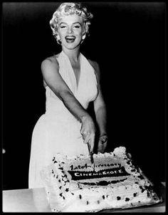 """15 Septembre 1954 / Cette date marque le premier anniversaire du CinémaScope ; Marilyn coupe le gâteau aux côtés de Walter WINCHELL et DiMAGGIO. Earl WILSON et Gina LOLLOBRIGIDA sont également conviés à la cérémonie se déroulant au """"Trans-Lus Theater"""". Le premier des procédés de film large projeté sur grand écran qui ait connu un grand succès commercial (""""La Tunique"""", de H. KOSTER, 1953).  Le CinémaScope est fondé sur un procédé optique très ancien, l'anamorphose, qui, par un jeu de miroirs…"""