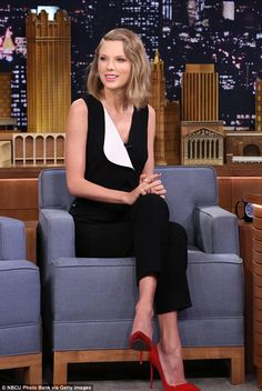 Taylor appearing on The Tonight Show in a pair of cropped black tailored pants with a sleeveless black vest featuring a white lapel