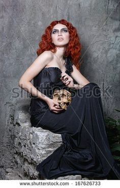 Red-haired vampire girl posing with a skull in her hands in urban twilight @shutterstock