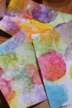 """1tb water, 1 tsp acrylic, a """"big squirt"""" dish washing liquid. Mix in cups and blow bubbles. Put paper on top of bubbles. Switch colors to cover your paper. We are going to use this as a background for straw painting. If you have a lot of bubble bottles, which I do, you can add the acrylic paint."""