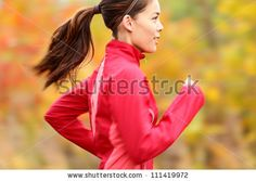 Running in Fall. Runner woman jogging in autumn forest. Beautiful young fit fitness sport model jogging with slight motion blur. Mixed race ...