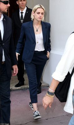 Funky: Kristen added a relaxed touch to her menswear inspired ensemble with a pair of trainers and multiple layered necklaces