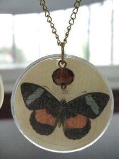 Detalle de uno de los colgantes de mariposas hechos con cristales antiguos de relojes de bolsillo.