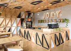 Prison converted into a residential complex, featuring a coffee shop that represents the site's bleak past but brings it to life through bright colourful geometric plywood cladding.    Jury Cafe by Biasol Design Studio